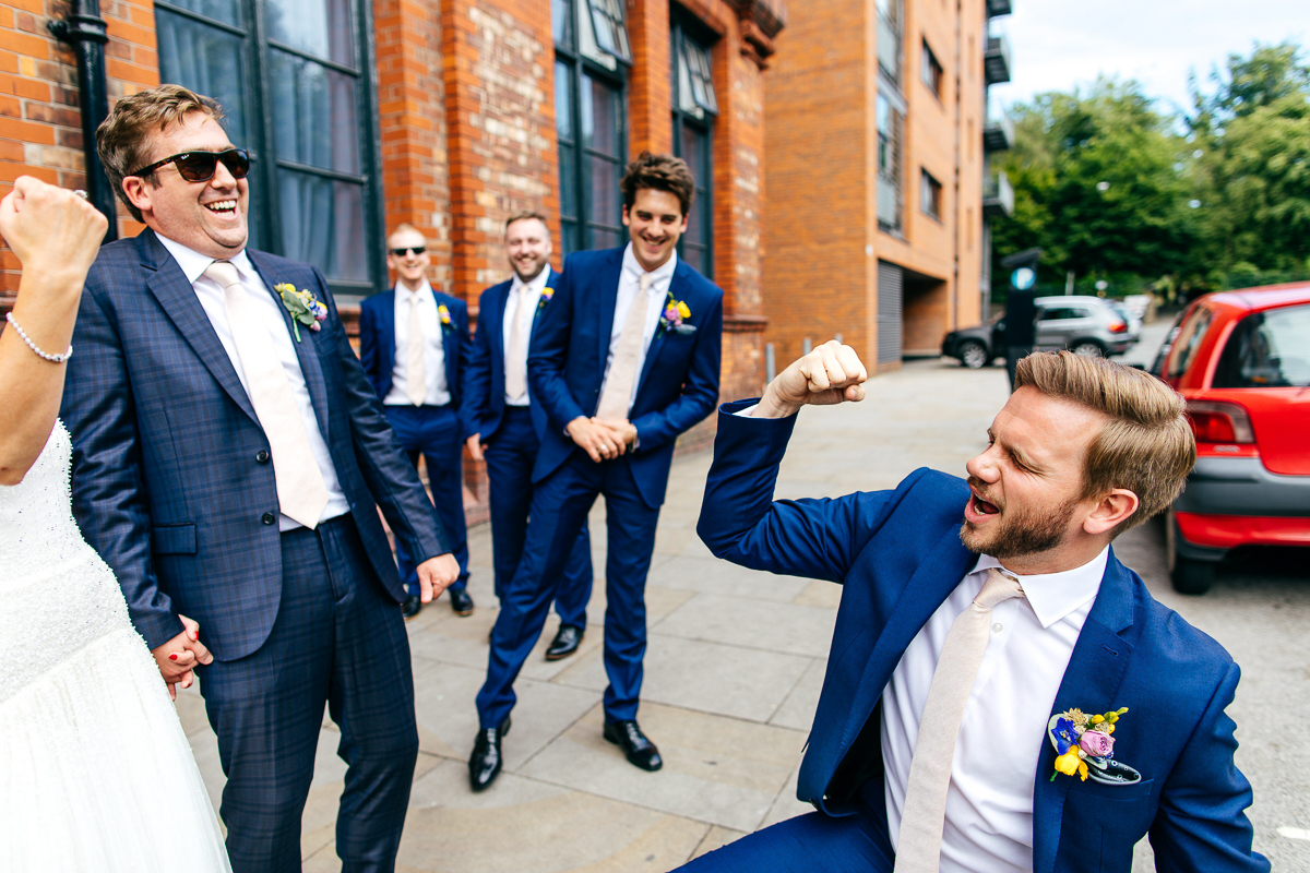 groom-fistpumps-colourful-buttonhole-blue-suit-ivory-tie-london-wedding-photographer