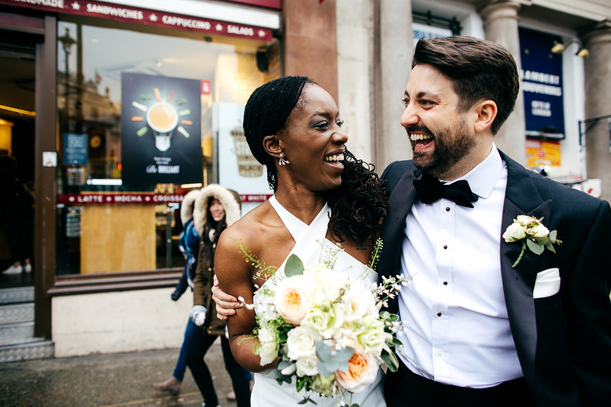 couple-laugh-together-street-photogrpahy-style-groom-wearing-black-dickie-bow