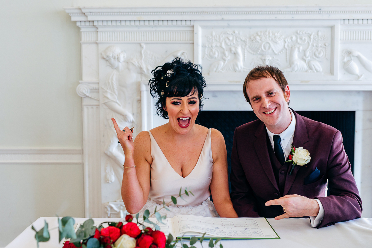 signing-register-quirky-bride-mod-style-groom-wears-burgundy-suit-london-wedding