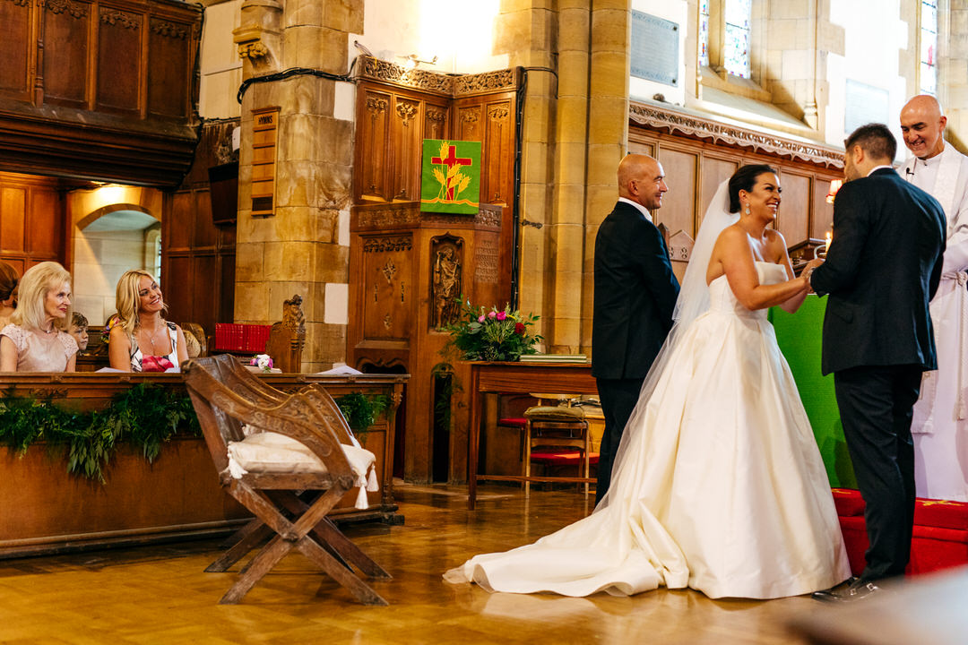 Couple at alter in Rossall School Ceremony laughing through their joyous ceremony