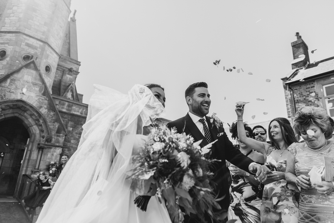 Black and white action shot of the confetti dash after their exit - just married at Rossall School