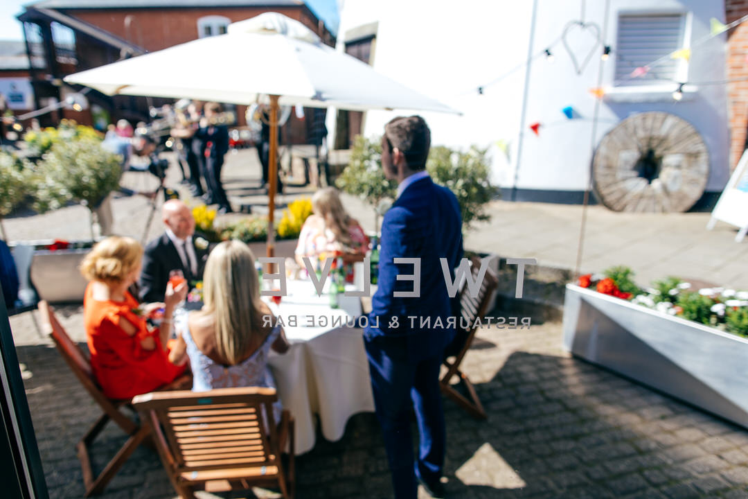 Twelve Restaurant wedding reception - view through the window at guest relaxing and drinking in the sunshine