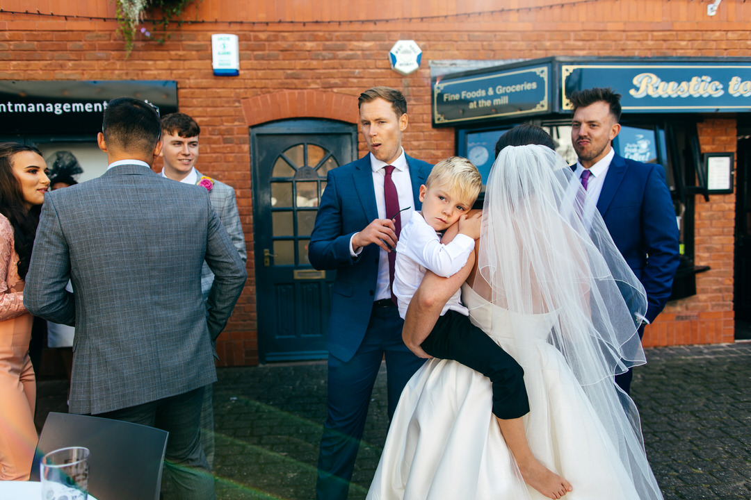 Guests chatting at Twelve Restaurant wedding bride carrying one of her children