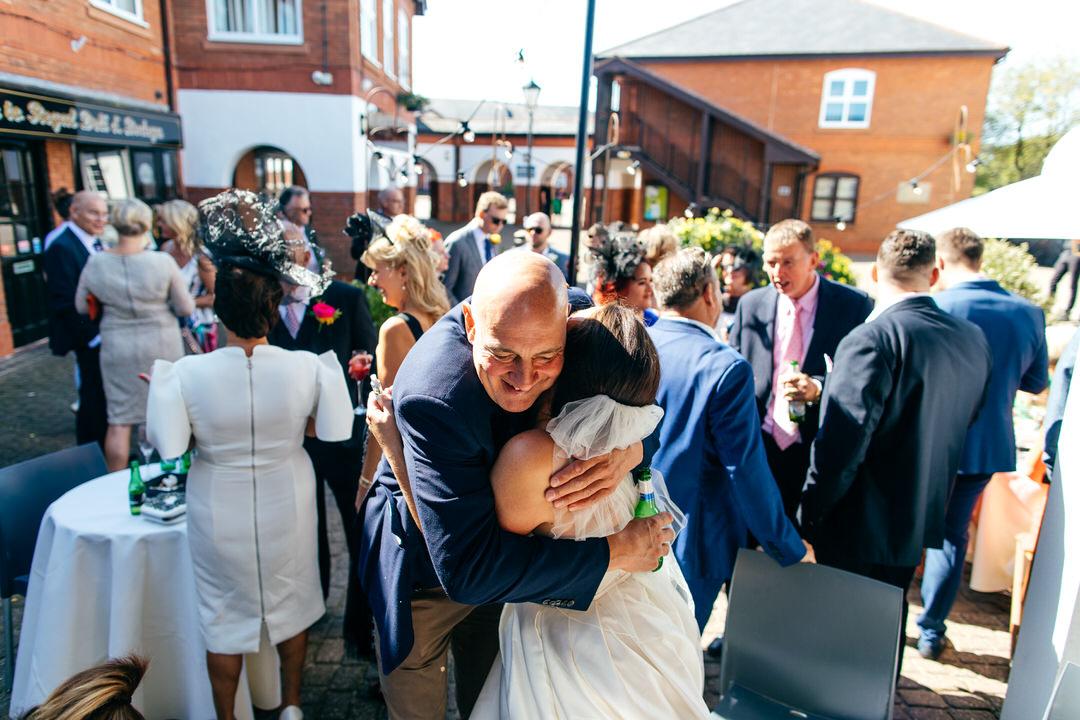Guests give bride a hug in Caroline Castigliano dress outside Twelve Restaurant wedding