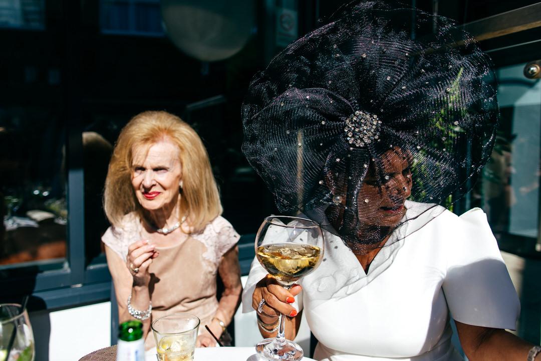 Nans in big hats enjoying big wines outside Twelve Reaturant Wedding in Thornton Cleveleys