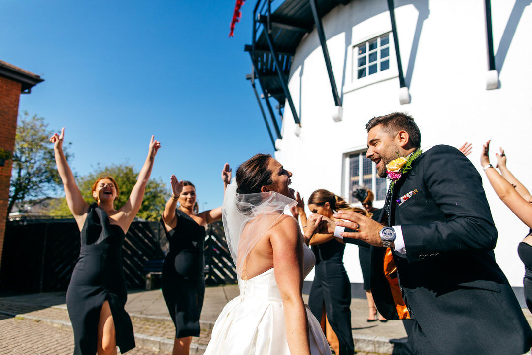 Bride and groom dancing by windmill to New York Brass Band at their raucous summer wedding at Twelve Restaurant