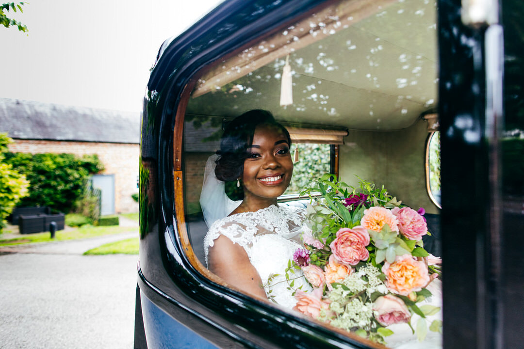 bride-sits-smiling-in-classic-car-holding-bouquet