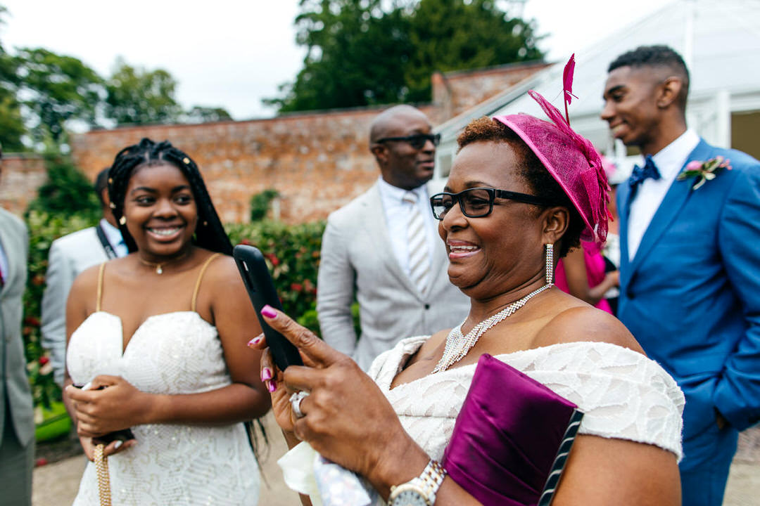 wedding-guest-wears-pink-hat-combermere-abbey