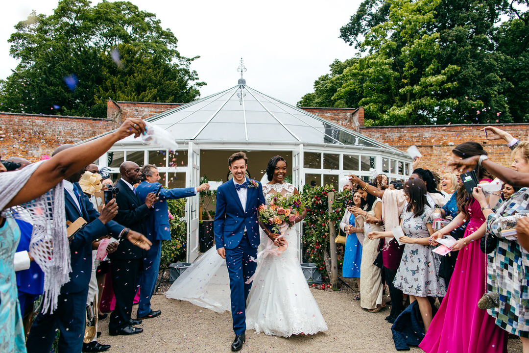 confetti-tunnel-bride-groom-smiling-combermere-abbey-shoes-of-prey