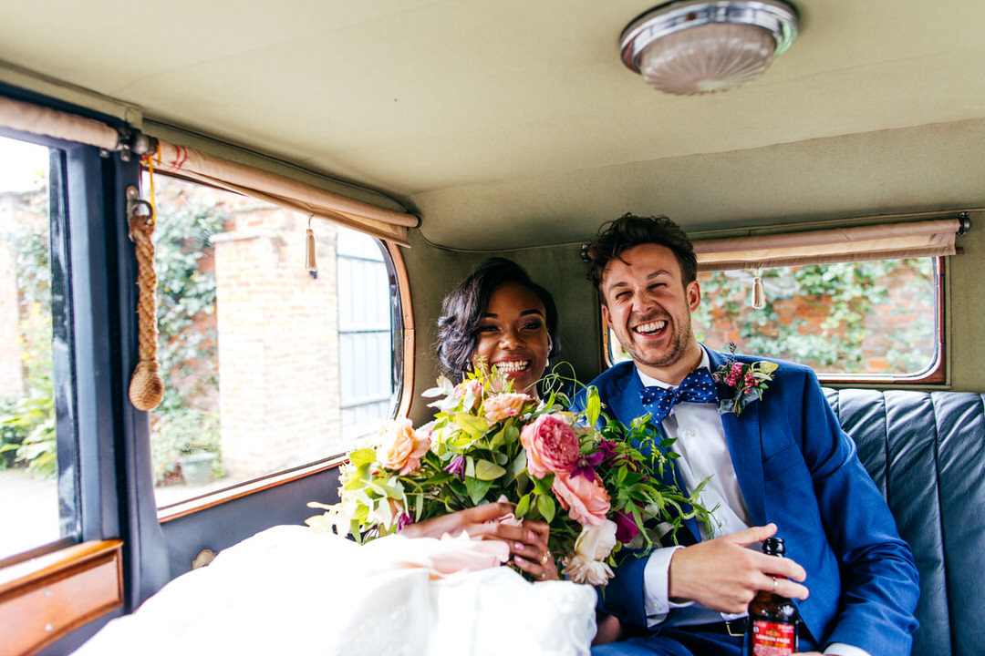 bride-and-groom-in-back-of-classic-car-laughing-together-one-stylish-day