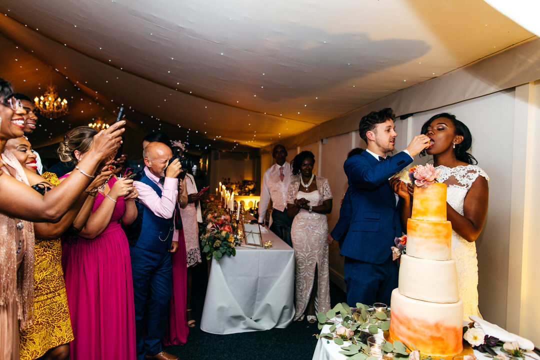 groom-feeds-bride-after-cake-cutting-in-marquee