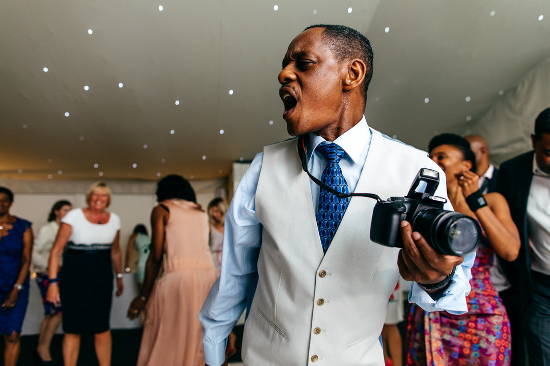 well-dressed-wedding-guest-with-camera-on-dancefloor