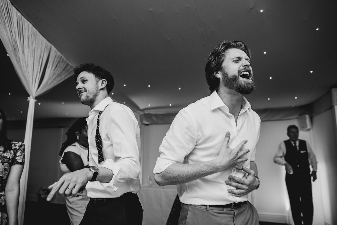 guests-on-dancefloor-singing-dancing-black-and-white