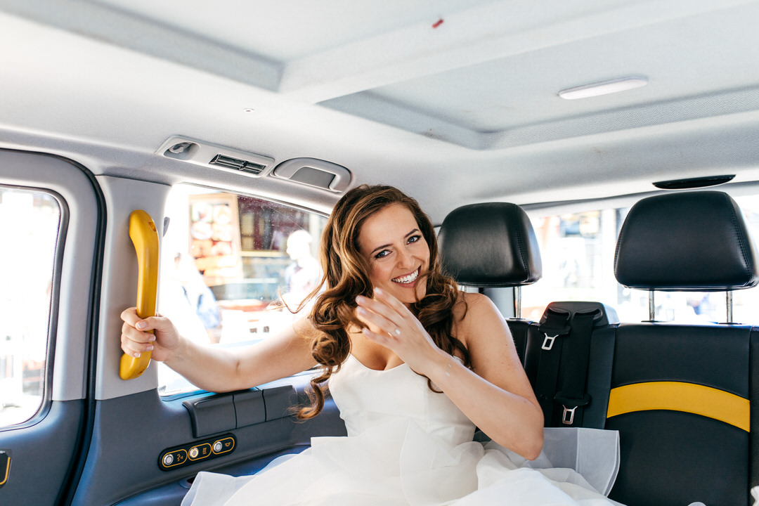 bride-taking-black-cab-london-wedding-photographer