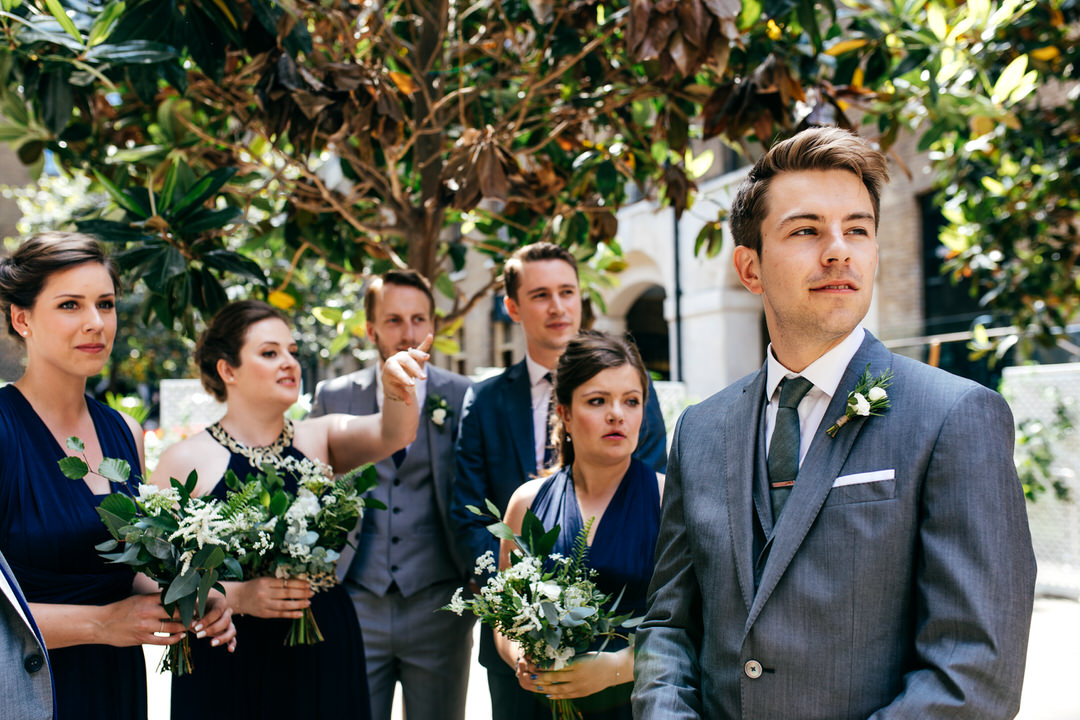 groom-waiting-bridesmaids-holding-flowers