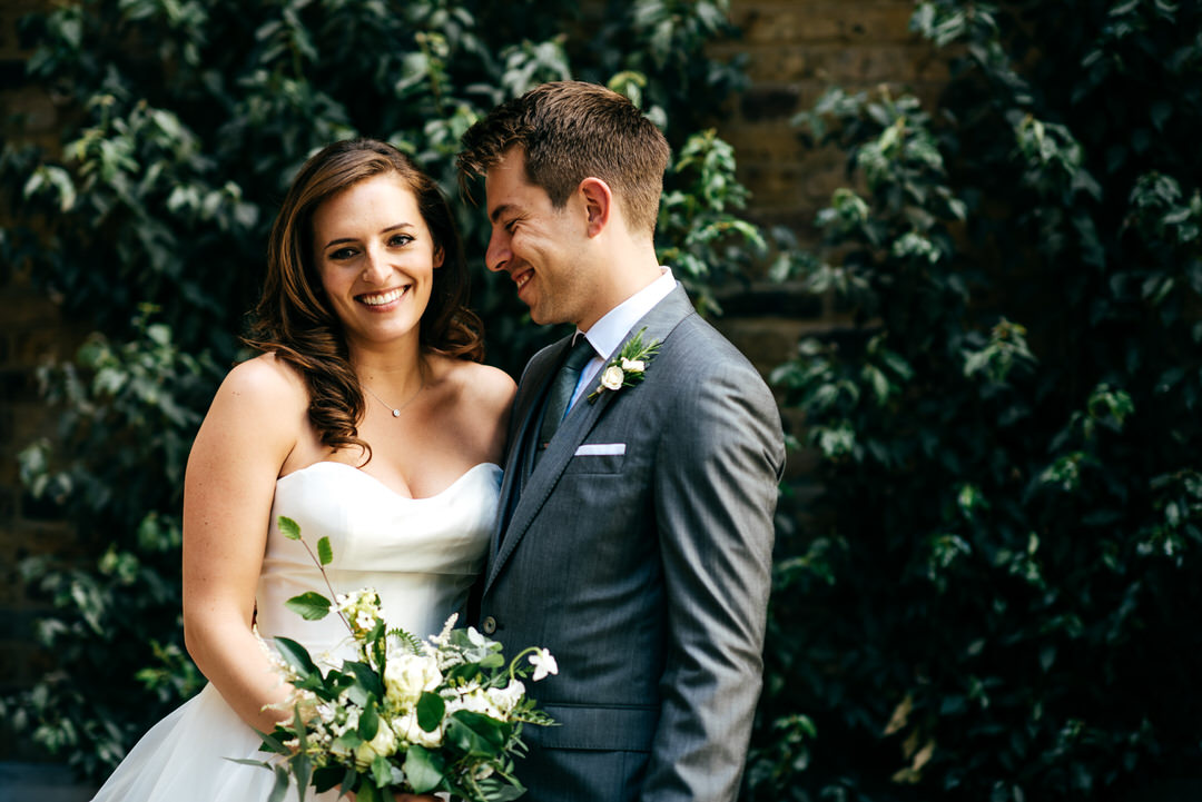 couple-surrounded-with-green-leaves-smiling-devonshire-terrace-wedding