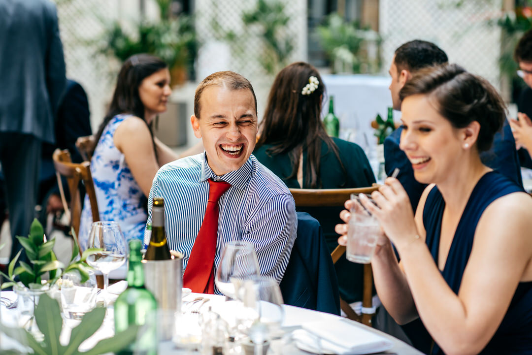 guest-in-stripy-shirt-laughs-with-bridesmaid-devonshire-terrace