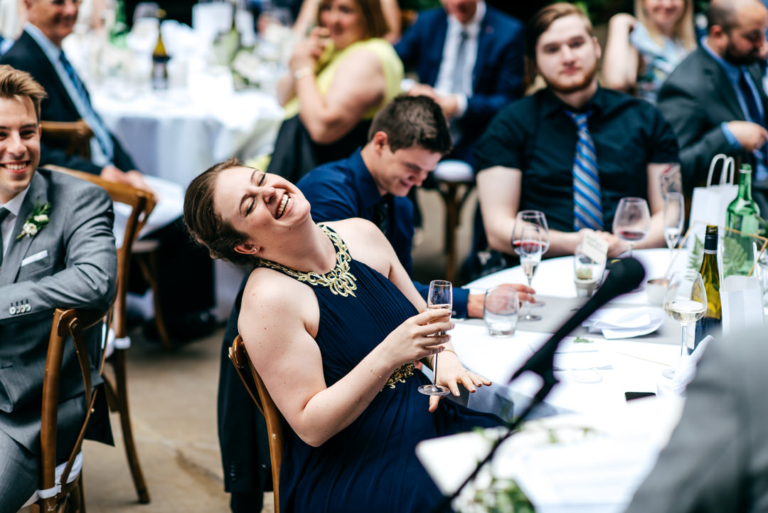 bridesmaid-wearing-navy-blue-and-gold-dress-laughing-speeches
