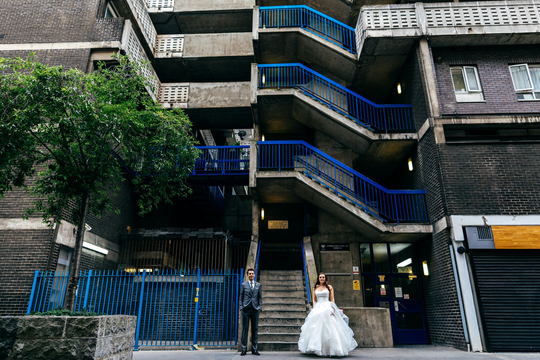 couple-photographed-under-blue-stairs-outside-creative-wedding-photography