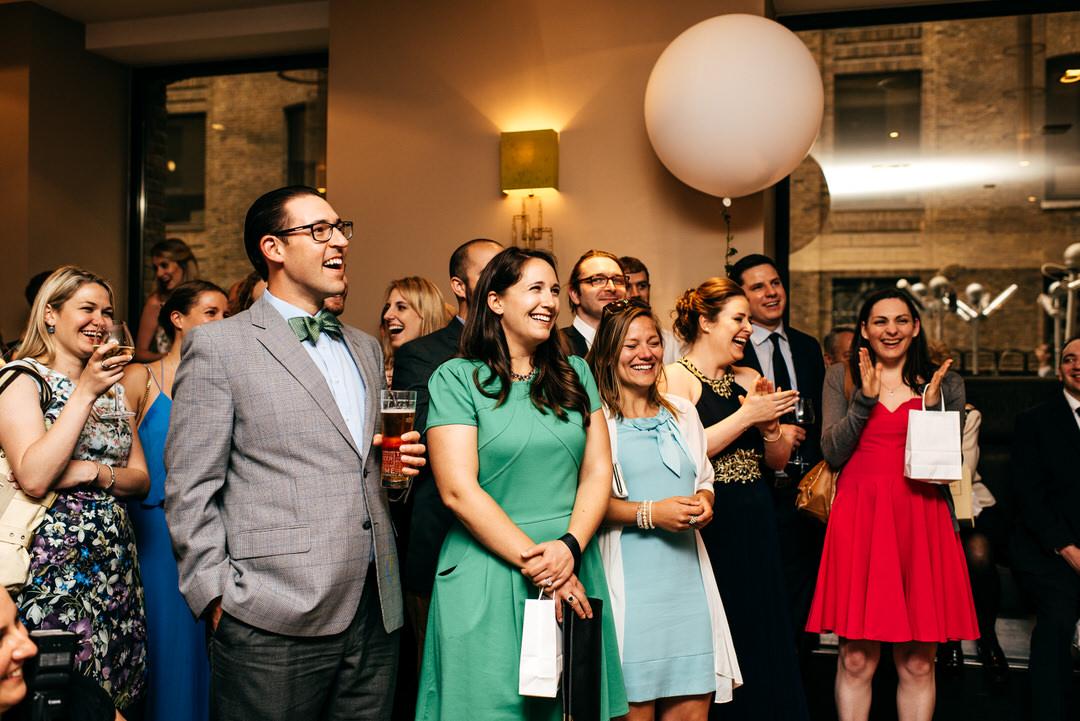laughing-guests-listening-grooms-speech-jewish-wedding