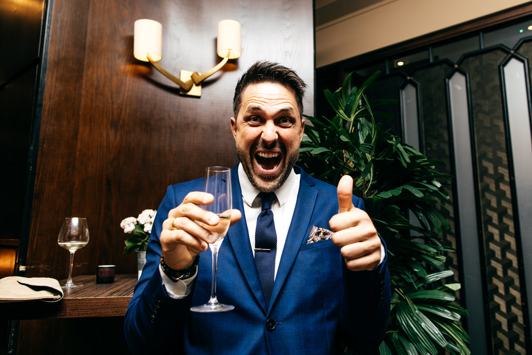 funny-guest-blue-suit-gives-thumbs-up-holding-champagne