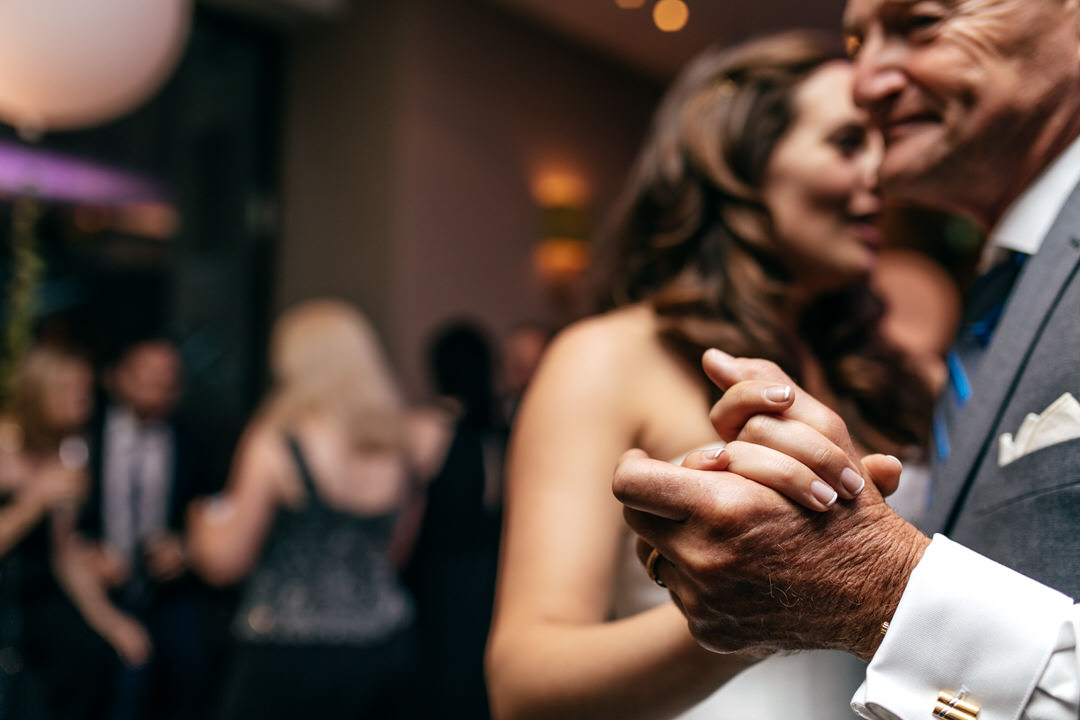 brides-father-holds-hands-during-dancing-london-wedding-devonshire-terrace