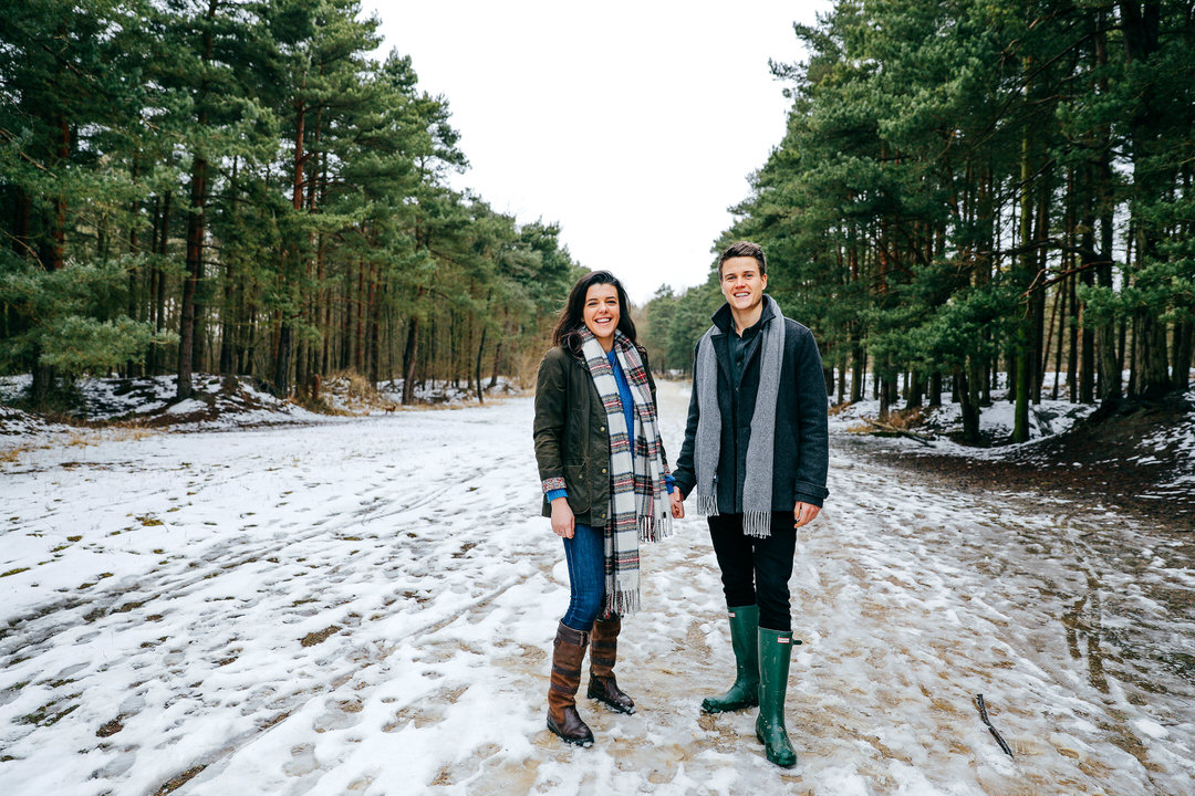 Couple stood hand in hand in Irchester Park in Northamptonshire with a sprinkle of snow