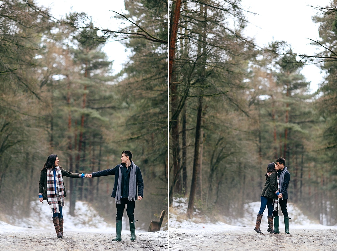 Engaged couple hand in hand and having a kiss in pine forest in Northamptonshire