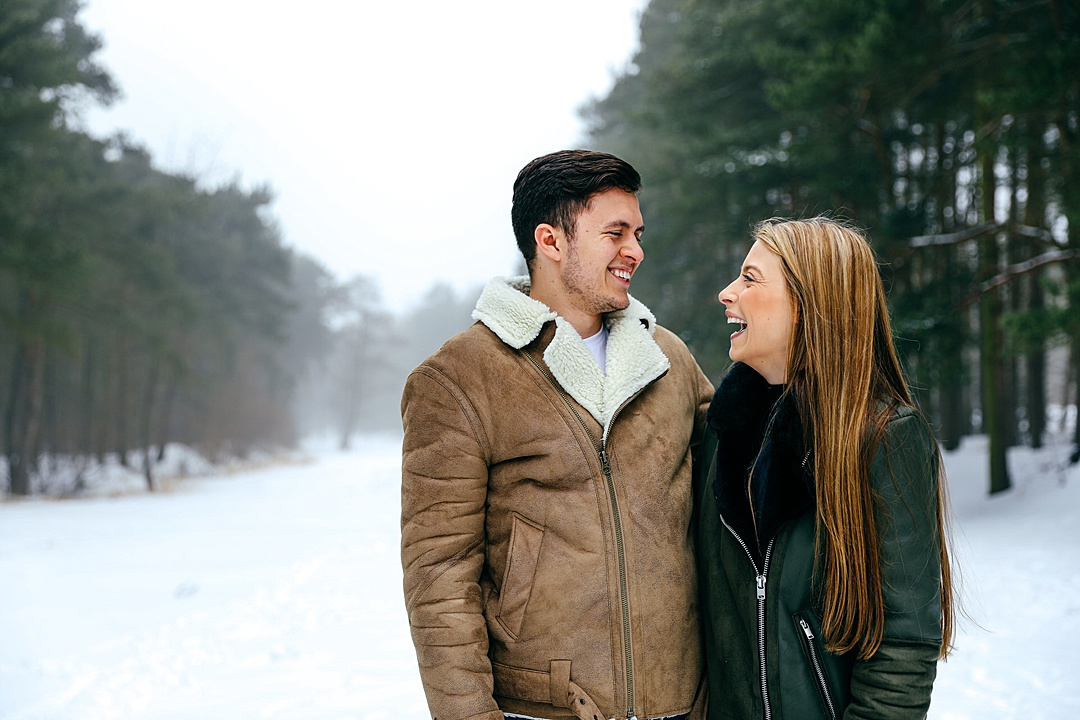 Couple facing each other laughing in the snow in Northamptonshire