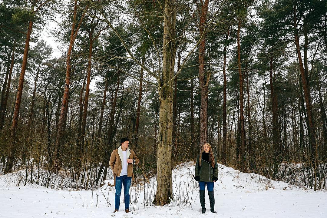 Couple on their snowy engagement shoot in Northamptonshire stood either side of a tree