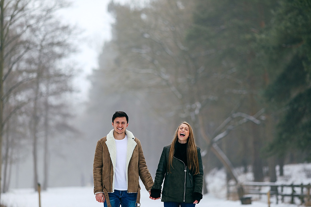 Couple hand in hand in the snow on their snowy e shoot