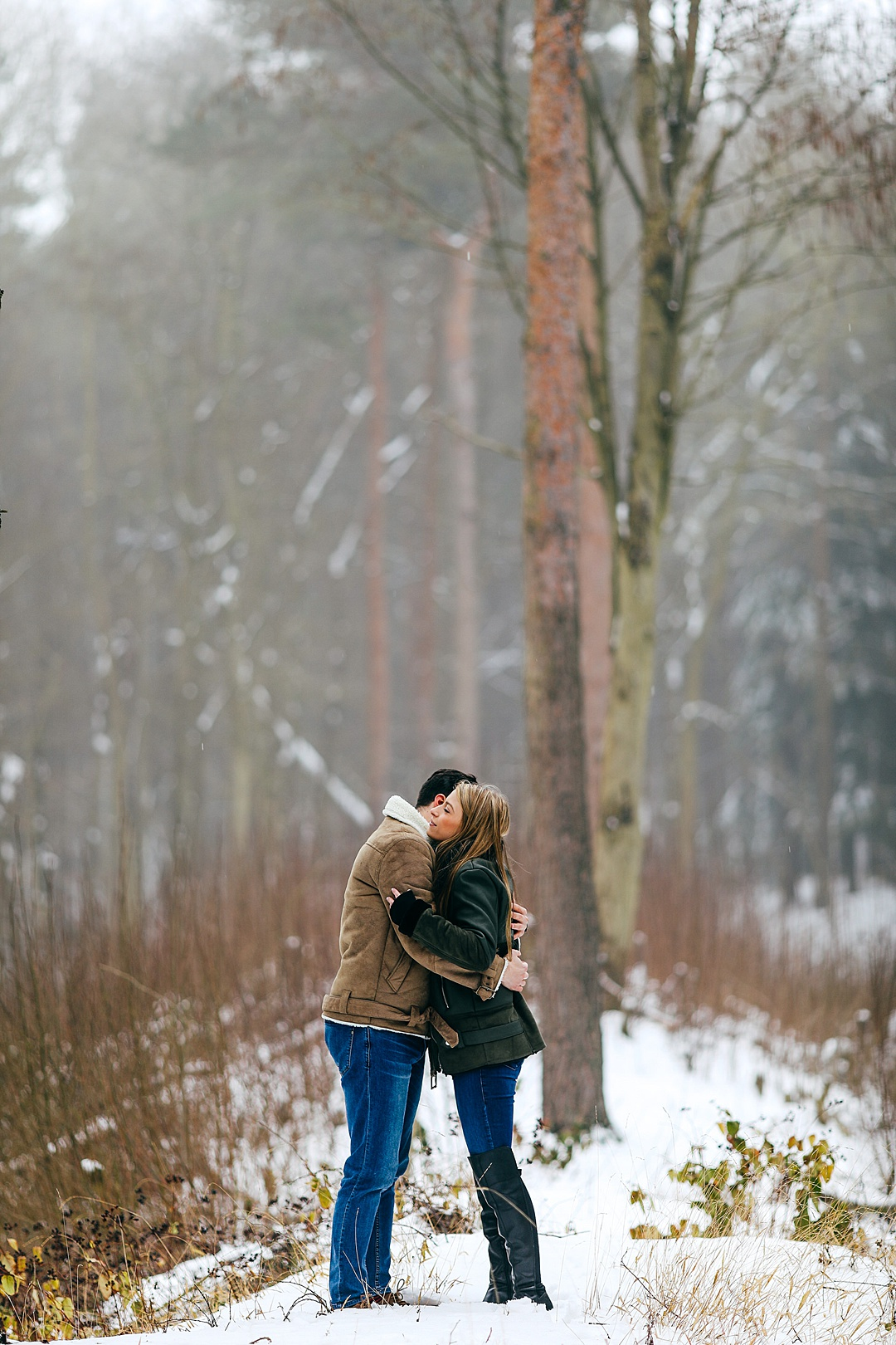 Couple hugging in the snowy woodland in Northamptonshire
