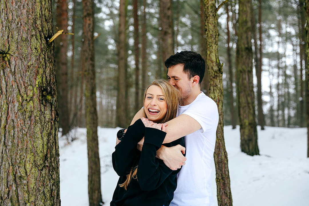 Couple cuddling in the snow in the woods girl looking at camera laughing