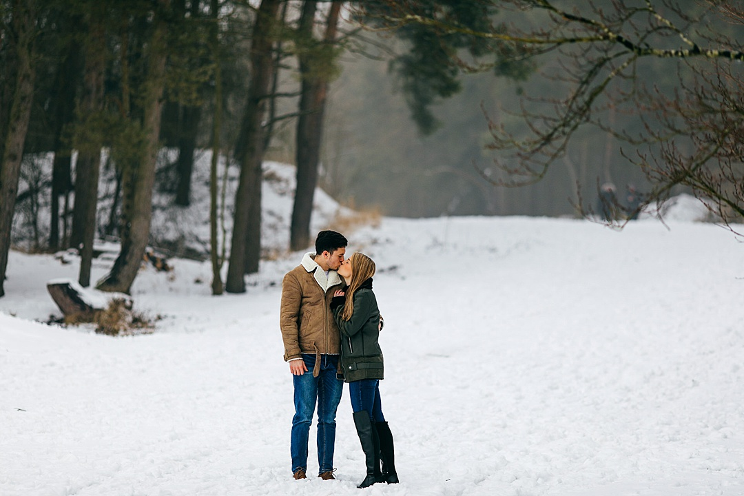 Romantic shot of couple kissing in the snow in Northamptonshire at Irchester Country Park